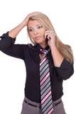 Besorgte Frau, die zu ihrem Handy hört Stockfotografie