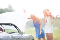 Besorgte Freundinnen, die aufgegliedertes Auto am sonnigen Tag überprüfen lizenzfreies stockbild
