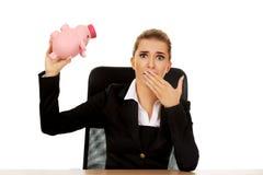 Besorgte Geschäftsfrau mit einem piggybank hinter dem Schreibtisch lizenzfreie stockfotos