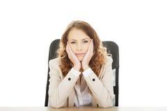 Besorgte Geschäftsfrau am Schreibtisch stockbild