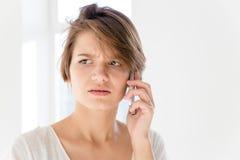 Besorgte gestörte junge Frau, die am Handy spricht Lizenzfreies Stockfoto