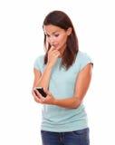 Besorgte hübsche Frau, die einen Text liest Lizenzfreie Stockfotos
