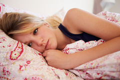 Besorgte Jugendliche, die im Bett liegt Lizenzfreie Stockfotografie