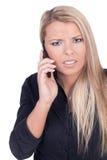 Besorgte junge blonde Frau, die am Handy spricht Lizenzfreies Stockfoto