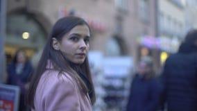 Besorgte junge Frau, die auf gedrängte Straße geht und sich herum, Paranoia dreht stock footage