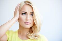 Besorgte junge Frau, die ihren Kopf hält Lizenzfreie Stockbilder