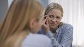 Besorgte junge Frau, die Pickel auf Gesicht vor Spiegel, Unsicherheit zerquetscht stock video