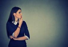 Besorgte junge Frau, die zur Seite schaut Lizenzfreies Stockbild