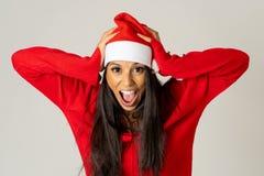 Besorgte junge Frau in Weihnachtsmann-Hut schreiend im Druck, der unzeitgemäß für Weihnachten läuft stockbild