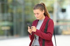Besorgte junge Geschäftsfrau, die ein Telefon verwendet Lizenzfreie Stockfotos