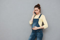 Besorgte junge schwangere Frau, die am Handy spricht Stockbilder