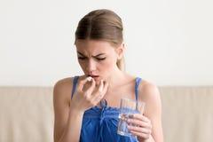 Besorgte kranke Frau, die zu Hause Pille, Glas Wasser hält stockbild