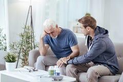 Besorgte männliche Pflegekraft, die älteren Mann sich beruhigt lizenzfreie stockfotos