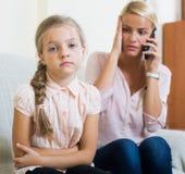 Besorgte Mutter, die Doktor für Tochter mit Bauchschmerzen anruft Lizenzfreies Stockfoto