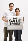 Besorgte Paar-Holding für Verkaufs-Zeichen Lizenzfreie Stockfotos