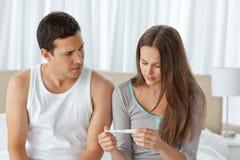 Besorgte Paare, die eine Schwangerschaftprüfung betrachten Stockfotografie