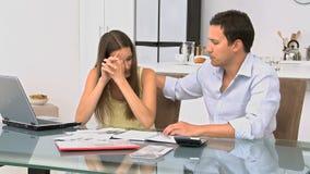 Besorgte Paare, die ihre Rechnungen berechnen stock footage