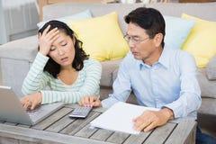 Besorgte Paare, die Rechnungen überprüfen Stockbilder