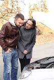 Besorgte Paare, die unter der Haube des Zusammenbruchautos schauen Stockfotografie