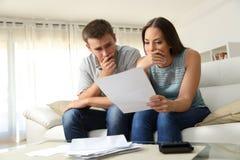 Besorgte Paare, die zu Hause einen Brief lesen stockbild