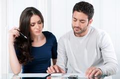 Besorgte Paare mit Rechnungen Stockbild