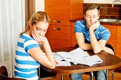 Besorgte Paare nach den Rechenrechnungen, die zu Hause sitzen Lizenzfreies Stockbild
