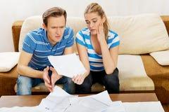 Besorgte Paare nach den Rechenrechnungen, die zu Hause sitzen Lizenzfreies Stockfoto