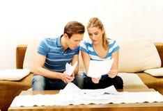 Besorgte Paare nach den Rechenrechnungen, die zu Hause sitzen Stockbild