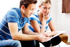 Besorgte Paare nach den Rechenrechnungen, die zu Hause sitzen Lizenzfreie Stockfotos