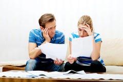 Besorgte Paare nach den Rechenrechnungen, die zu Hause sitzen Stockfoto