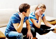 Besorgte Paare nach den Rechenrechnungen, die zu Hause sitzen Lizenzfreie Stockfotografie