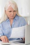 Besorgte reife Frau mit Laptop-Rechenhaushalts-Finanzen lizenzfreies stockbild