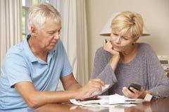 Besorgte reife Paare, die Finanzen überprüfen und zusammen Rechnungen durchlaufen Lizenzfreies Stockbild