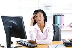 Besorgte schwarze Geschäftsfrau am Schreibtisch Stockfoto