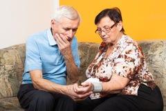 Besorgte Senioren, die Blutdruck messen Stockfoto