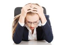 Besorgte, traurige Geschäftsfrau, die durch die Tabelle sitzt. stockbilder