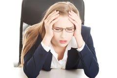 Besorgte, traurige Geschäftsfrau, die durch die Tabelle sitzt. Stockbild