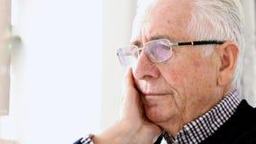 Besorgter älterer Mann, der zu Hause im Stuhl sitzt stock footage