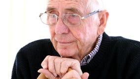 Besorgter älterer Mann mit dem Spazierstock, der zu Hause im Stuhl sitzt stock footage