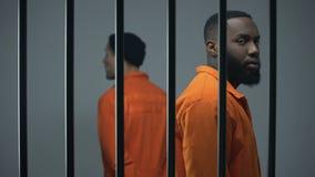 Besorgter Afroamerikaner und europäische Gefangene auf Kante des Konflikts in der Gefängniszelle stock video footage