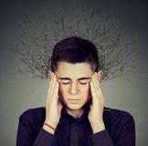 Besorgter betonter Mann mit dem Gehirn, das in Linien Fragezeichen schmilzt Stockbild