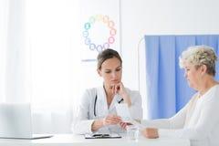 Besorgter Doktor und ihr Patient lizenzfreie stockfotografie