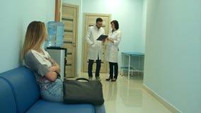 Besorgter Frauenpatient, der ins Krankenhaushalle während zwei Doktoren besprechen Diagnose wartet stock footage