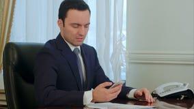 Besorgter Geschäftsmann, der auf Smartphone schaut und schlechte Nachrichten liest stock video