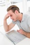 Besorgter Geschäftsmann, der mit Laptop arbeitet Lizenzfreie Stockbilder