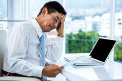 Besorgter Geschäftsmann, der an seinem Schreibtisch arbeitet Lizenzfreie Stockfotografie