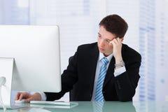 Besorgter Geschäftsmann, der Computer auf Schreibtisch betrachtet Lizenzfreies Stockfoto