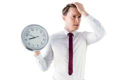 Besorgter Geschäftsmann, der eine Uhr hält Stockfotos