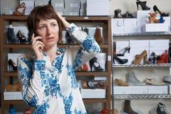 Besorgter Inhaber des Schuhgeschäfts am Telefon Stockfotografie