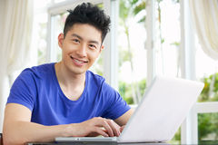 Besorgter junger chinesischer Mann, der zu Hause Laptop verwendet Lizenzfreies Stockfoto